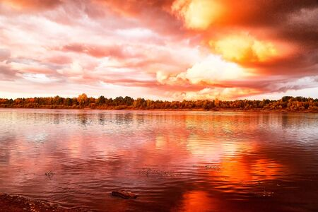 Foto de Sky with fantastic, amazing, stormy, disturbing red clouds over the river on a summer or autumn evening. Dramatic landscape with sky full of cloud at sunset - Imagen libre de derechos