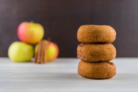 Photo for Stack of Three Apple Cider Donuts with Apples in Background - Royalty Free Image