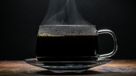 Steaming Glass Coffee Cup Centered over wooden table