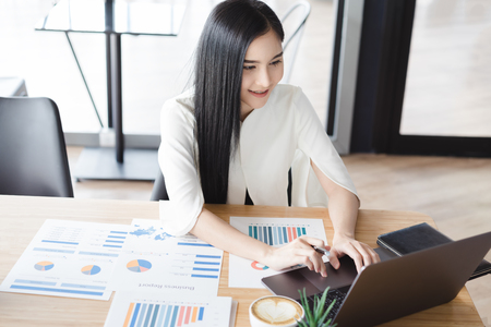 Foto de Asian beautiful young business woman in white shirt smiling working on desk with laptop and financial report document. - Imagen libre de derechos