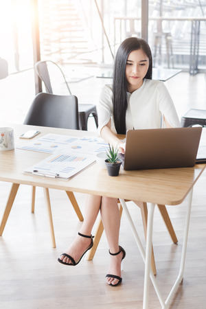 Photo for Asian beautiful young business woman in white shirt smiling working on desk with laptop and financial report document. - Royalty Free Image