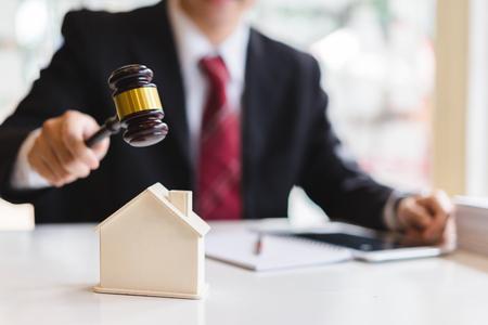 Foto de Auctioneer knocking down a model house with his gavel, Property sale auction concept - Imagen libre de derechos