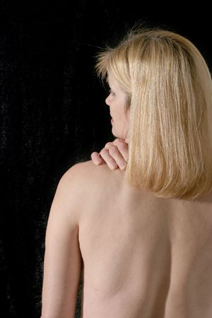 Upper back of beautiful, sexy blonde woman on black background rubbing and massaging her back or neck pain\r