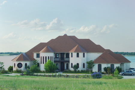 Large and beautiful modern style house with tile roof and castle turrets on a small lake.