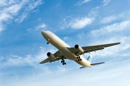 Passenger airplane landing against blue cloudy sky