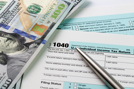 Photo pour Filling out income tax forms with US dollar and pen - image libre de droit