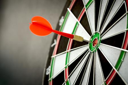 Foto de Right on target concept using dart in the bullseye on dartboard - Imagen libre de derechos