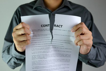 Photo for Businessman ripping a contract down to the centre - Royalty Free Image