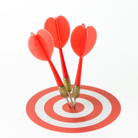 Foto de Three red darts pinned right on the center of target - Imagen libre de derechos