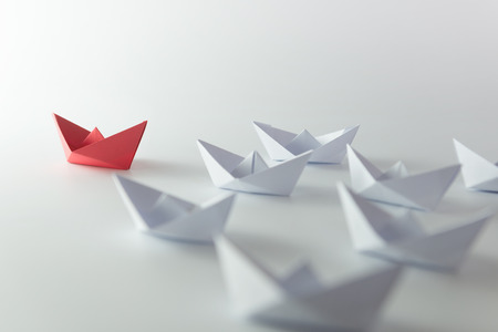 Photo pour Leadership concept using red paper ship among white - image libre de droit