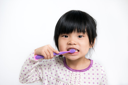 Foto de Little Asian girl in pyjamas brushing teeth - Imagen libre de derechos