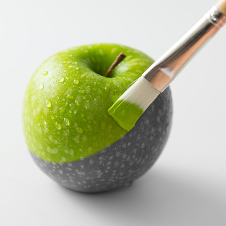 Photo pour Painting a fresh green apple with paintbrush - image libre de droit