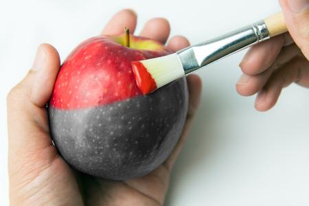 Foto de Painting a fresh red apple with paintbrush - Imagen libre de derechos