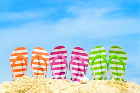 Foto de Row of multicolor flip flops on beach against blue sky - Imagen libre de derechos