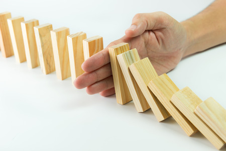 Photo pour Solution concept with hand stopping wooden blocks from falling in the line of domino - image libre de droit