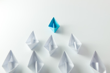 Photo pour Leadership concept with blue paper ship leading among white - image libre de droit