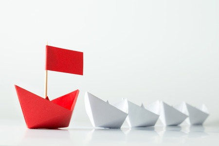 Photo pour Leadership concept with red paper ship leading among white - image libre de droit