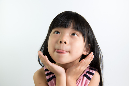 Photo for Asian child shows delicious expression with tongue out - Royalty Free Image