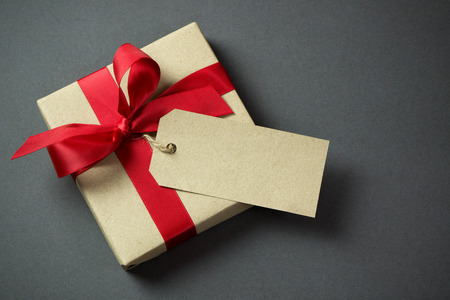 Photo for Rustic gift box with empty tag and red bow - Royalty Free Image