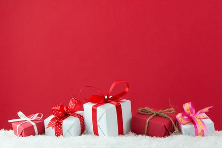 Foto de Holiday presents with ribbon in a row on snow with red color background - Imagen libre de derechos