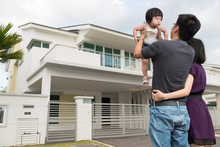 Photo for Young parents with toddler standing in front of modern residential area - Royalty Free Image
