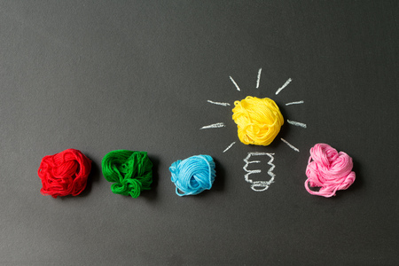 Photo pour Light bulb in a row of multicolor yarn balls over black background - image libre de droit