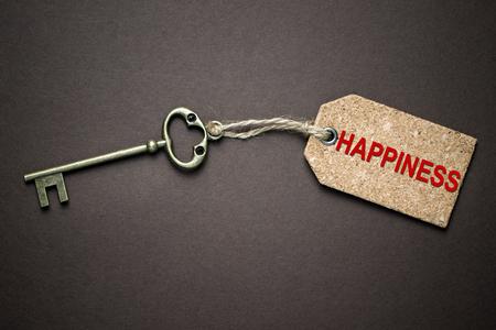 Foto de The key of happiness isolated over black background - Imagen libre de derechos