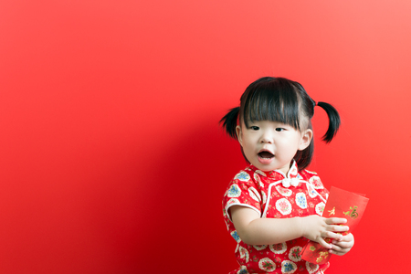 Photo pour Little Asian girl holding red envelope on red background - image libre de droit