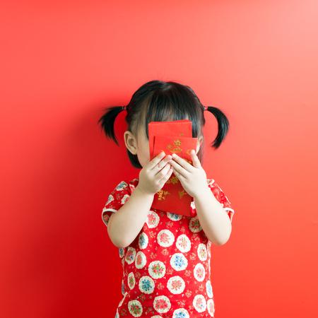 Foto de Little Asian girl holding red envelope on red background - Imagen libre de derechos