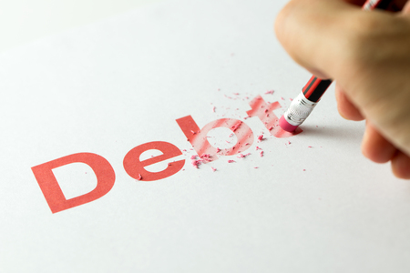 Photo pour Close up of red pencil erasing the word debt on paper - image libre de droit