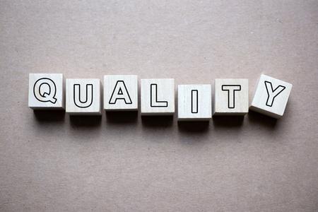 Foto de Quality word written on wood block isolated on grunge paper background - Imagen libre de derechos