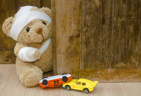 Foto de Teddy bear with bandages and toy car upside down on wood background with copy space,Accident concept. - Imagen libre de derechos