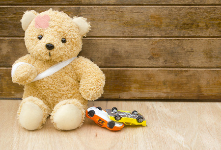 Foto de Teddy bear with bandages and toy cars upside down on wood background with copy space,Accident concept. - Imagen libre de derechos