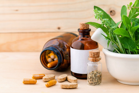 Foto de Alternative health care fresh herbal  ,dry and herbal capsule with mortar on wooden background. - Imagen libre de derechos