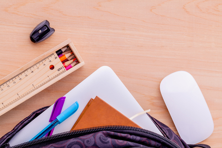 Foto de Backpack with school supplies laptop,book stationary,mouse,pen,ruler, and color pencil on wooden table . - Imagen libre de derechos