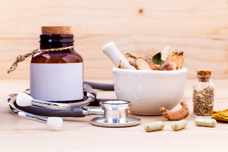 Photo pour Capsule of herbal medicine alternative healthy care with stethoscope on wooden background. - image libre de droit