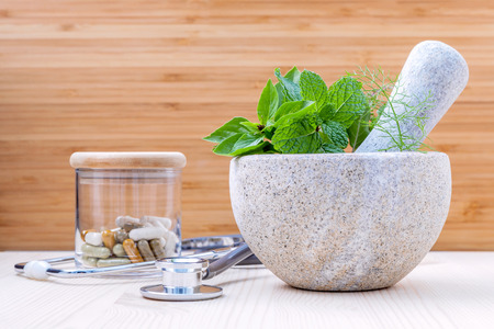 Foto de Fresh herbal leaves basil ,sage , mint ,holy basil ,fennel and capsule of herbal medicine alternative health care with stethoscope setup on wooden background. - Imagen libre de derechos