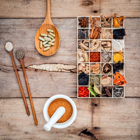 Foto de Alternative health care dried various Chinese herbs in wooden box and herbs capsule in wooden spoon with mortar on old wooden background. - Imagen libre de derechos