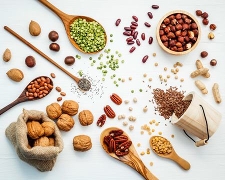 Foto de Bowls and spoons of various legumes and different kinds of nuts walnuts kernels ,hazelnuts, almond kernels,brown pinto ,soy beans ,flax seeds ,chia ,red kidney beans and pecan set up on white wooden table. - Imagen libre de derechos