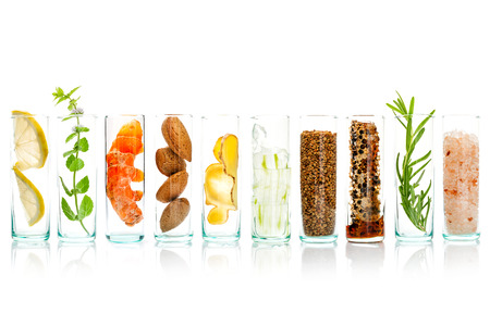Foto de Homemade skin care and body scrubs with natural ingredients aloe vera ,lemon,cucumber ,himalayan salt ,peppermint ,lemon slice,rosemary,almonds,ginger and honey pollen in glass bottles isolate on white background. - Imagen libre de derechos