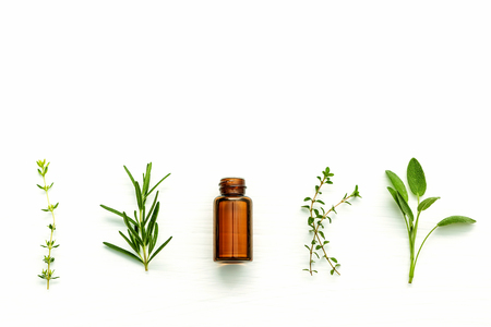 Photo for Bottle of essential oil with fresh herbal sage, rosemary, lemon thyme and thyme setup with flat lay on white wooden table. - Royalty Free Image
