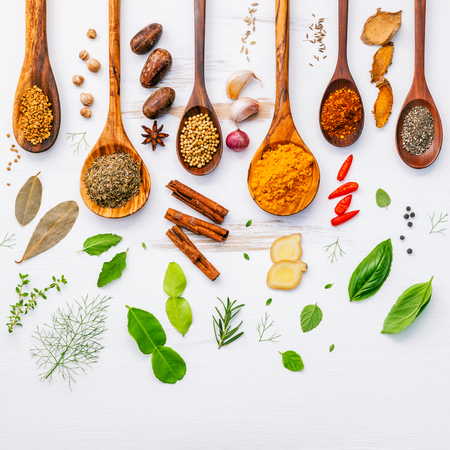 Photo for Various herbs and spices in wooden spoons. Flat lay of spices ingredients chilli ,pepper, garlic,dries thyme, cinnamon,star anise, nutmeg,rosemary, sweet basil and kaffir lime on wooden background. - Royalty Free Image