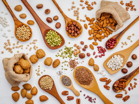 Foto de Various legumes and different kinds of nuts in spoons. Walnuts kernels ,hazelnuts, almond ,brown pinto ,soy beans ,flax seeds ,chia ,red kidney beans and pecan set up on white wooden table. - Imagen libre de derechos