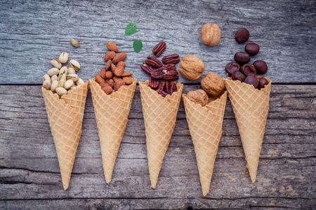 Foto de Concept for homemade various nuts ice cream. Mixed nuts in waffle cones on shabby wooden background.top view - Imagen libre de derechos