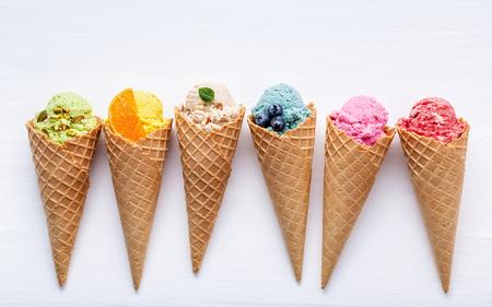 Foto de Various of ice cream flavor in cones blueberry ,strawberry ,pistachio ,almond ,orange and cherry setup on white wooden background . Summer and Sweet menu concept. - Imagen libre de derechos