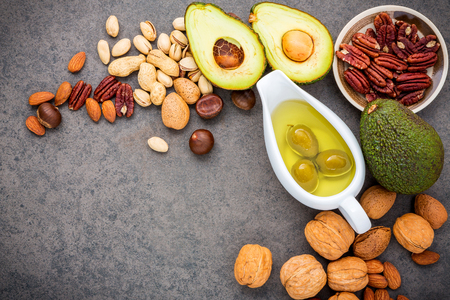 Foto de Selection food sources of omega 3 and unsaturated fats. Superfood high vitamin e and dietary fiber for healthy food. Almond ,pecan,hazelnuts,walnuts,olive oil,fish oil and salmon on stone background. - Imagen libre de derechos