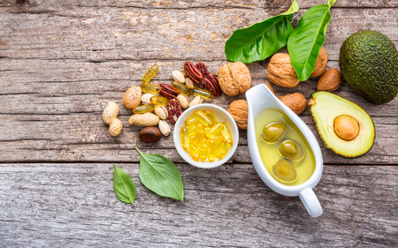 Photo pour Selection food sources of omega 3 and unsaturated fats. Superfood high vitamin e and dietary fiber for healthy food. Almond,pecan,hazelnuts,walnuts,olive oil,fish oil and salmon on wooden background. - image libre de droit
