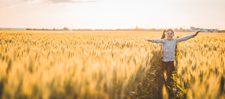 Foto de Little girl running cross the wheat field at sunset - Imagen libre de derechos