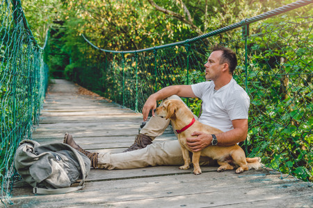 Photo for Hiker with small yellow dog resting on the wooden suspension bridge in the forest - Royalty Free Image