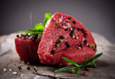 Photo for Raw beef steaks on wooden table - Royalty Free Image